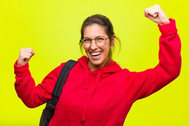 Jonge mooie student triomfantelijk schreeuwen, ziet eruit als opgewonden, blij en verrast winnaar, vieren