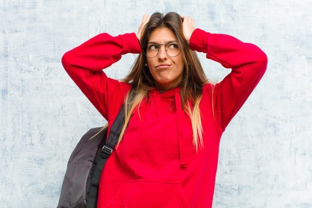 Jonge mooie student voelt zich gefrustreerd en geïrriteerd, ziek en moe van mislukking, beu met saaie, saaie taken
