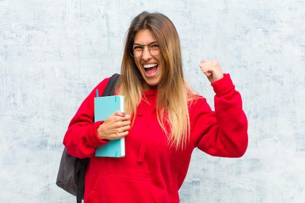 Jonge mooie student voelt zich gelukkig, positief en succesvol, viert overwinning, prestaties of geluk