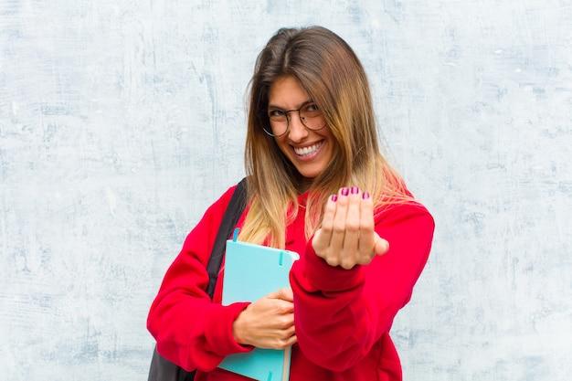Jonge mooie student voelt zich gelukkig, succesvol en zelfverzekerd, staat voor een uitdaging en zegt: kom maar op! of je verwelkomen