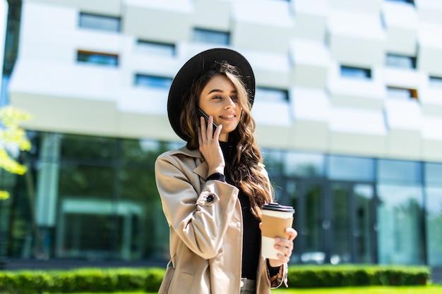 Jonge mooie studente door de universiteit die aan de telefoon spreekt
