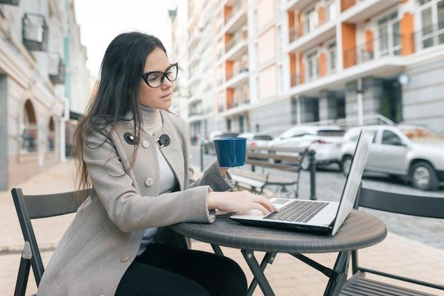 Jonge mooie studente in een openluchtkoffie met laptop