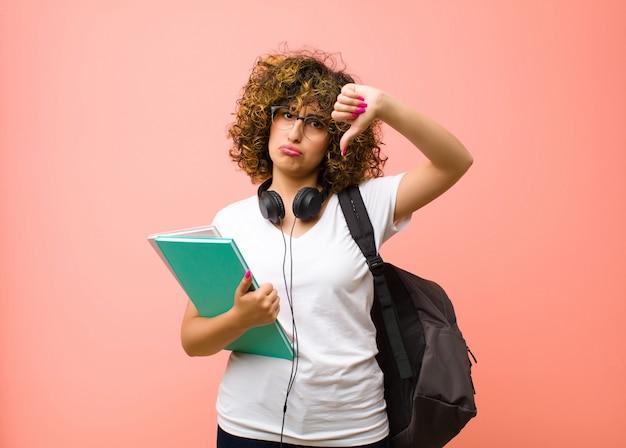 Jonge mooie studentenvrouw die droevig, teleurgesteld of boos kijken, die duimen neer in meningsverschil tonen, gefrustreerd over roze muur voelen