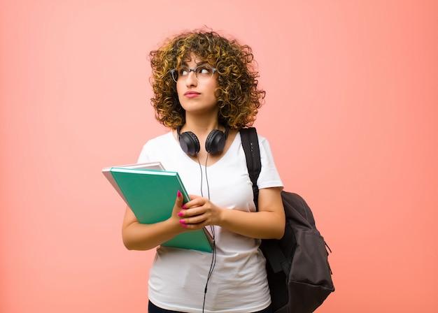 Jonge mooie studentenvrouw die nadenkend voelt, zich afvraagt of ideeën verbeeldt, dagdroomt en omhoog kijkt om ruimte tegen roze muur te kopiëren