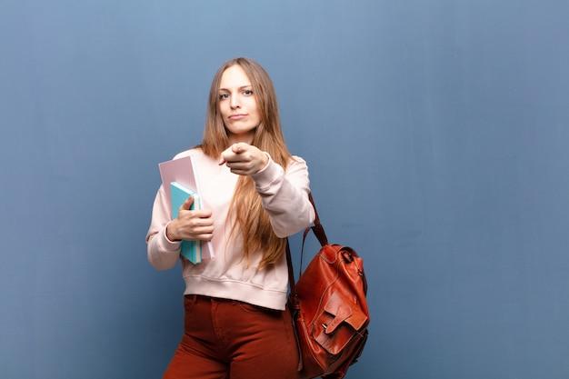 Jonge mooie studentenvrouw met boeken en zak blauwe muur met een copyspace