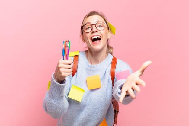 Jonge mooie studentenvrouw met gelukkige uitdrukking met open hand