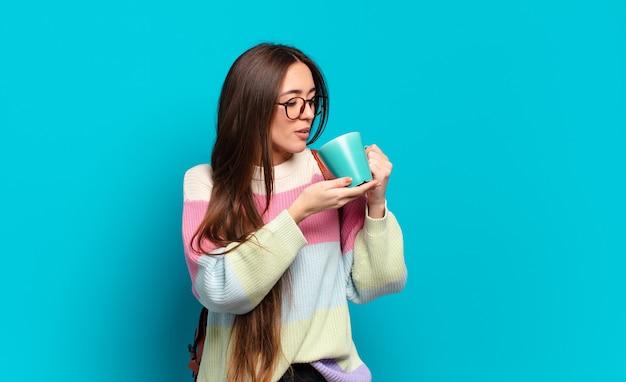 Jonge mooie studentenvrouw vrouw met een koffiekopje