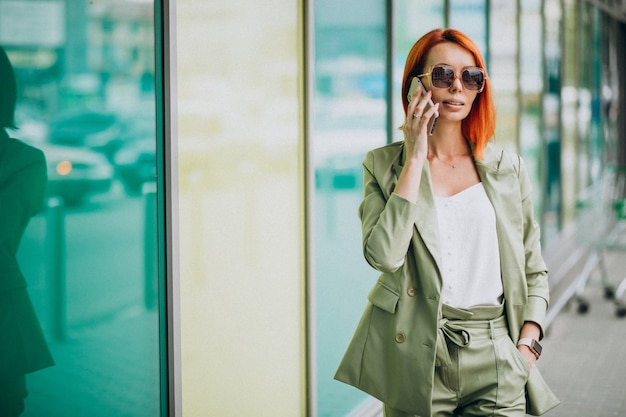 Jonge mooie succesvolle vrouw in groen pak praten aan de telefoon
