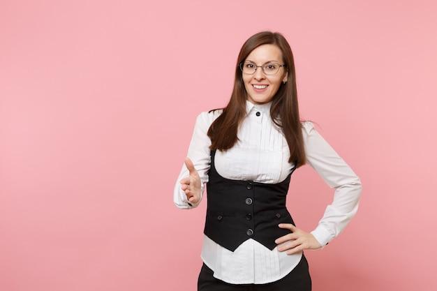 Jonge mooie succesvolle zakenvrouw in pak en bril hand geven voor handdruk geïsoleerd op pastel roze achtergrond. dame baas. prestatie carrière rijkdom concept. kopieer ruimte voor advertentie.
