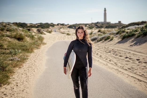 Jonge mooie surfer vrouw op het strand bij zonsondergang vuurtoren bij kaap trafalgar los spain