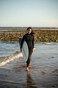 Jonge mooie surfer vrouw op het strand bij zonsondergang
