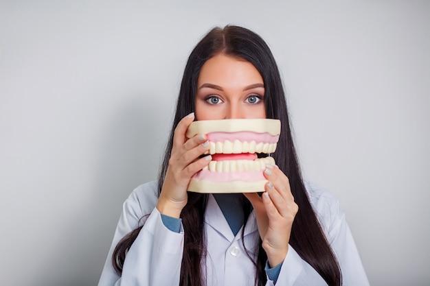 Jonge mooie tandarts doktor die een plastic gebit in een doos houdt.