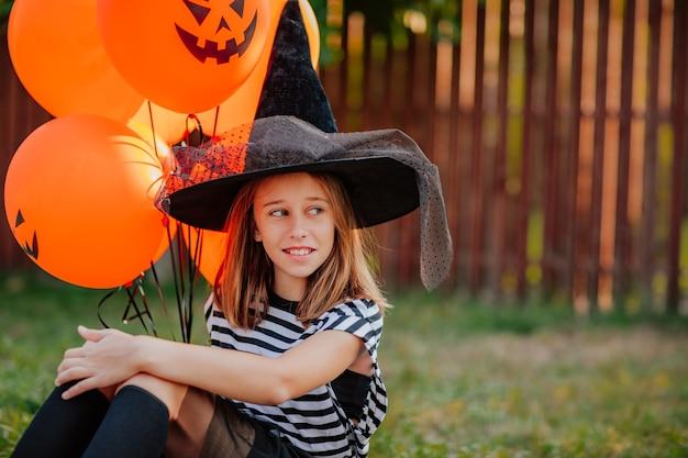 Jonge mooie tiener meisje in kostuum als een heks met zwarte hoed en gestript shirt poseren met een bos oranje halloween ballonnen zittend op straat. vakantieconcept.
