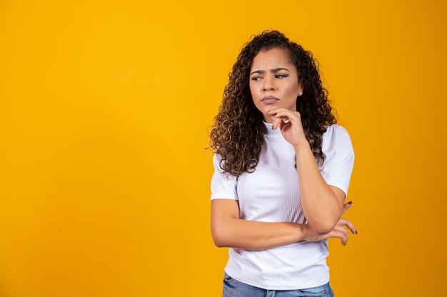 Jonge mooie tiener student meisje dromen denken in kant kijken over gele achtergrond.