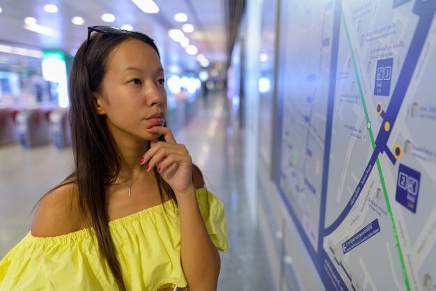 Jonge mooie toeristenvrouw die de stad van bangkok onderzoekt