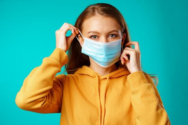 Jonge mooie toevallige vrouw die beschermend medisch masker draagt