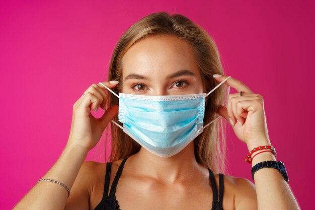 Jonge mooie toevallige vrouw die beschermend medisch masker tegen sinaasappel draagt