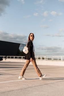 Jonge mooie trendy vrouw in modieuze vrijetijdskleding met stijlvolle tas in vintage zonnebril gaat op open parkeerplaats in de stad op zonnige zomerdag. modern meisjesmodel in elegante jeugdoutfit loopt buiten.