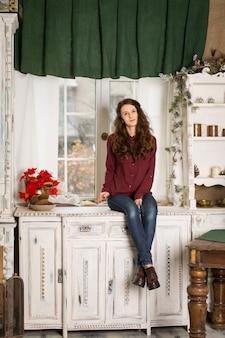 Jonge mooie trieste meisje zittend op een dressoir bij het raam.