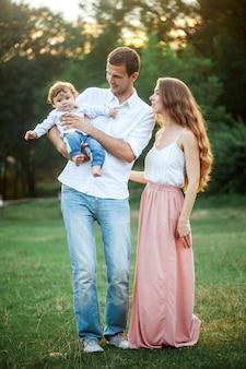 Jonge mooie vader, moeder en kleine peuterzoon tegen groene bomen