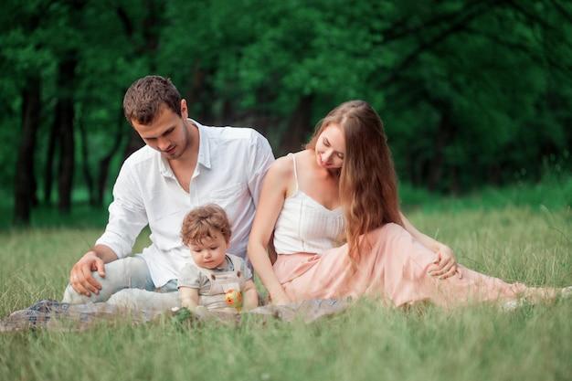 Jonge mooie vader, moeder en zoontje peuter tegen groene bomen