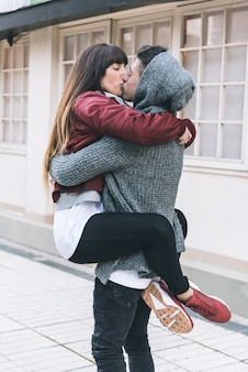 Jonge mooie verliefde paar knuffelen elkaar op een romantische manier in het midden van de straat
