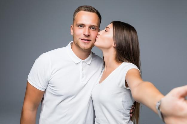 Jonge mooie verliefde paar nemen romantische zelfportret selfie foto samen met mobiele telefoon glimlachend gelukkig trendy kleding geïsoleerd op een grijze achtergrond