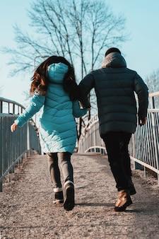 Jonge mooie verliefde paar wandelen in stadspark in de buurt van meer op valentijnsdag.