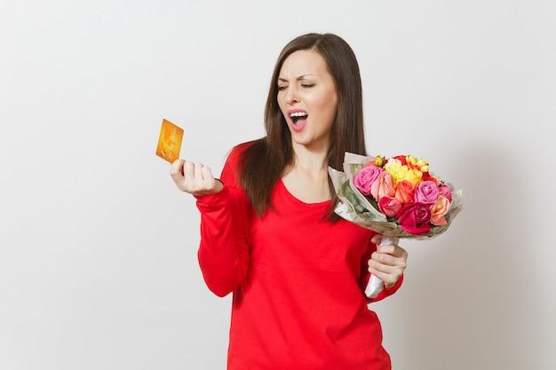 Jonge mooie verontwaardigde vrouw met boeket van mooie rozen bloemen creditcard geïsoleerd op een witte achtergrond. kopieer ruimte voor advertentie. st. valentijnsdag of internationale vrouwendag concept