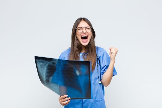 Jonge mooie verpleegster die agressief met een boze uitdrukking of met gebalde vuisten schreeuwt om succes te vieren