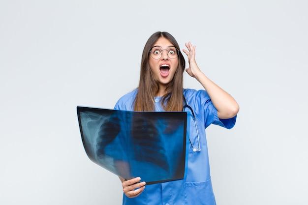 Jonge mooie verpleegster die met handen in de lucht gilt, zich woedend, gefrustreerd, gestrest en boos voelt