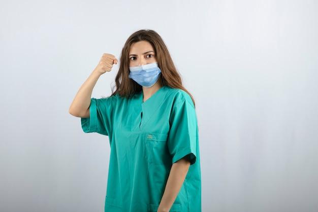 Jonge mooie verpleegster in groen uniform die een medisch masker draagt en een vuist toont