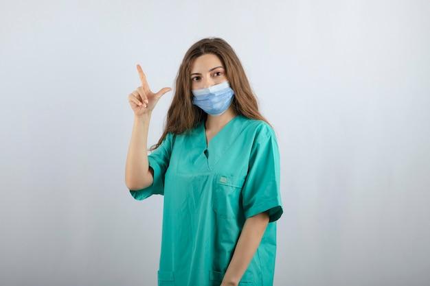 Jonge mooie verpleegster in groen uniform in een medisch masker dat omhoog wijst