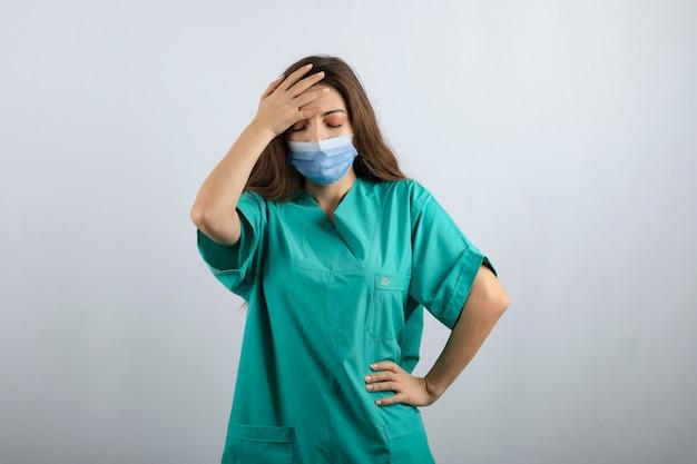 Jonge mooie verpleegster in groen uniform met een medisch masker