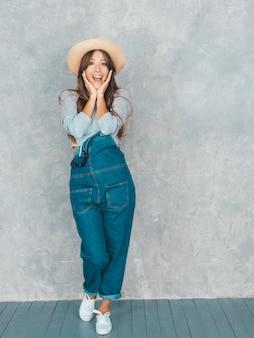Jonge mooie verraste vrouw die met handen dichtbij gezicht kijkt. trendy meisje in casual zomer overall kleding en hoed. het vrouwelijke stellen dichtbij grijze muur in studio