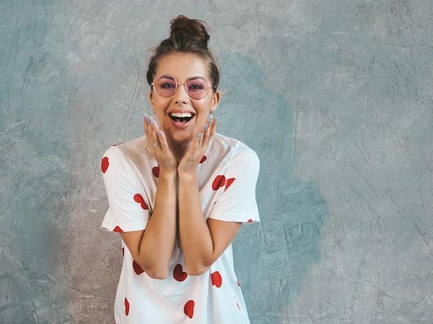Jonge mooie verraste vrouw die met handen dichtbij mond kijkt. trendy meisje in casual witte zomerjurk.