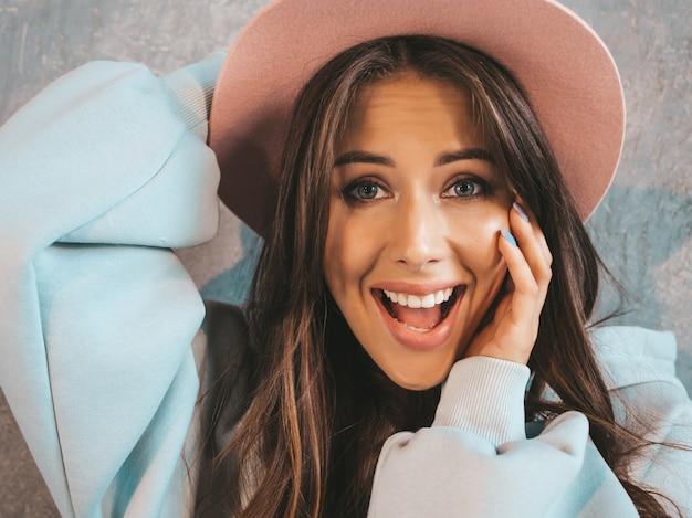 Jonge mooie verraste vrouw die met handen dichtbij mond kijkt. trendy meisje in casual zomer kleding en hoed. vrouw poseren in de buurt van grijze muur