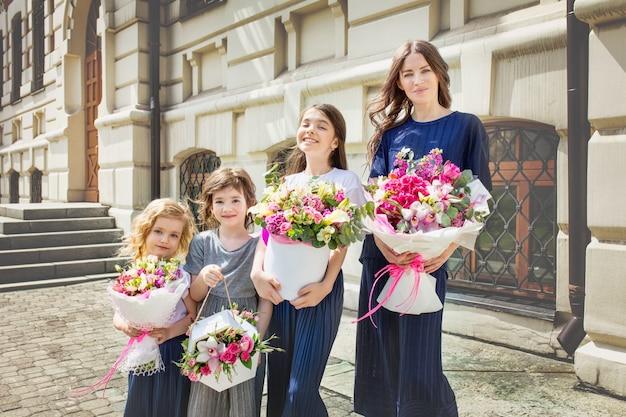 Jonge mooie volwassen moeder en haar kleine vrolijke en dochters lopen samen door de straten van de stad