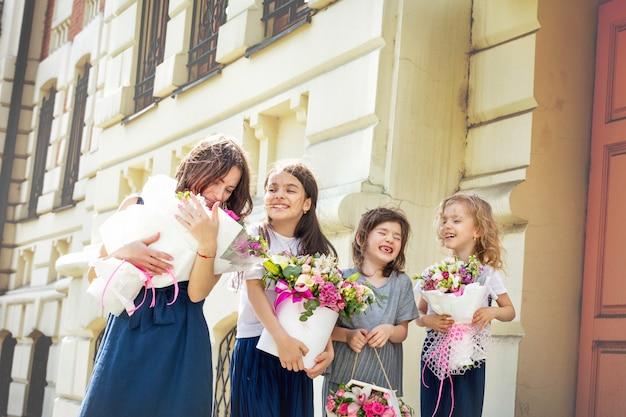 Jonge mooie volwassen moeder en haar kleine vrolijke en gelukkige dochters met boeketten bloemen