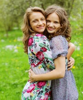 Jonge mooie vriendinnen over aardachtergrond, in de tuin