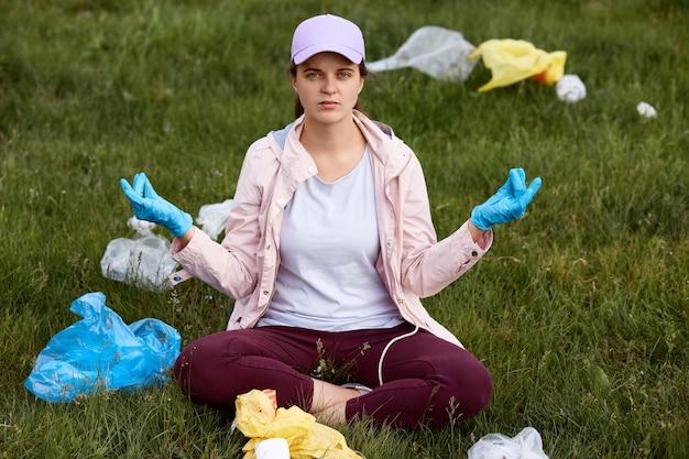 Jonge mooie vrijwilliger die zwerfafval opraapt in park, moe en boos is, probeert te ontspannen, in lotus houding op gras zit, camera kijkt, vrijetijdskleding draagt.