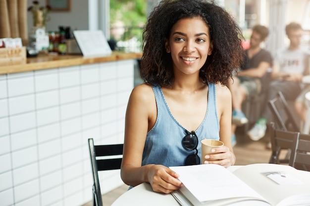 Jonge mooie vrolijke afrikaanse studente het glimlachen het lachen zitting in koffie. boeken tijdschriften liggen op tafel. leren en onderwijs.