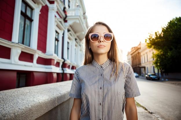 Jonge mooie vrolijke vrouw die in zonnebril stad rondwandelen