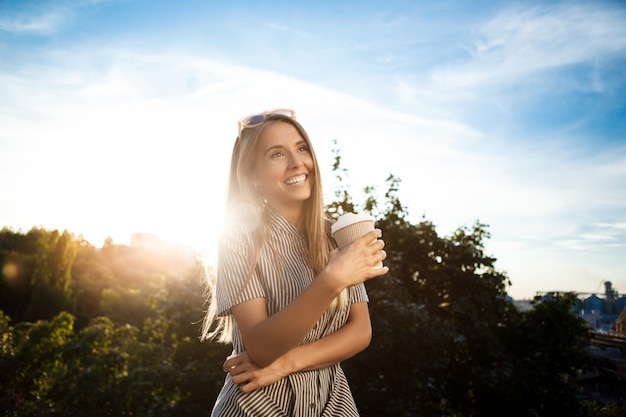 Jonge mooie vrolijke vrouw die rond stad lopen, glimlachen, die koffie houden.
