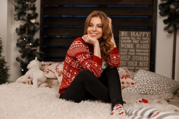 Jonge mooie vrolijke vrouw in modieuze rode trui zit op het bed