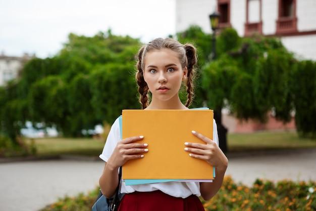 Jonge mooie vrolijke vrouwelijke student, die omslagen in openlucht houdt