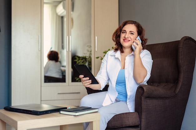 Jonge mooie vrouw 30 jaar oud in een wit overhemd werkt, zittend in een stoel in het kantoor aan huis en bespreekt problemen met de klant via videobellen