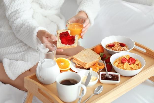 Jonge mooie vrouw aan het ontbijt op bed