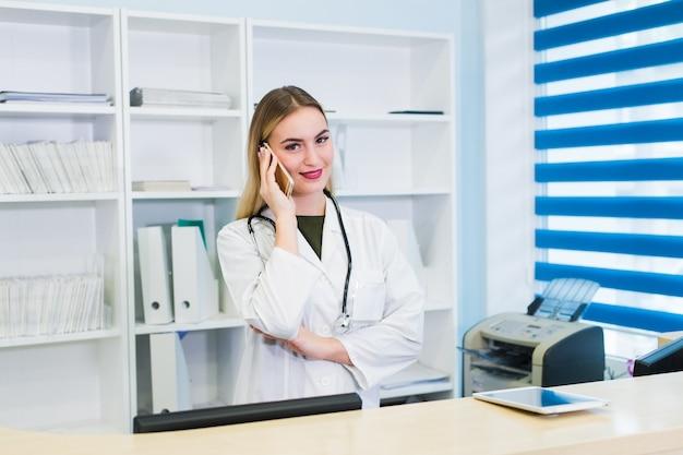 Jonge mooie vrouw arts die op telefoon spreekt