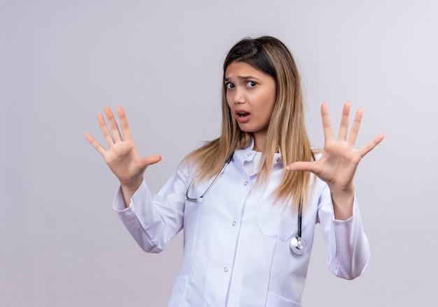 Jonge mooie vrouw arts die witte jas met stethoscoop draagt die bang maakt defensiegebaar maakt dat open handpalmen opheft